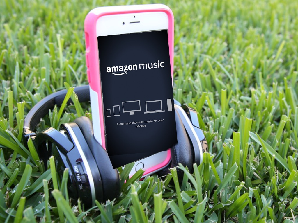 Phone in the grass playing amazon music with headphones by it