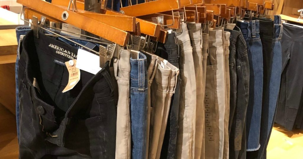 In store display of women's jeans on rack on hangers