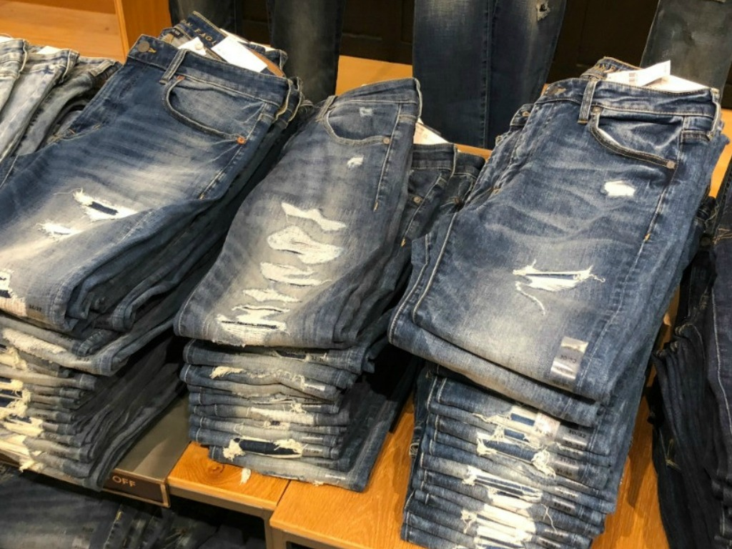 jeans in a stack on a shelf in a store