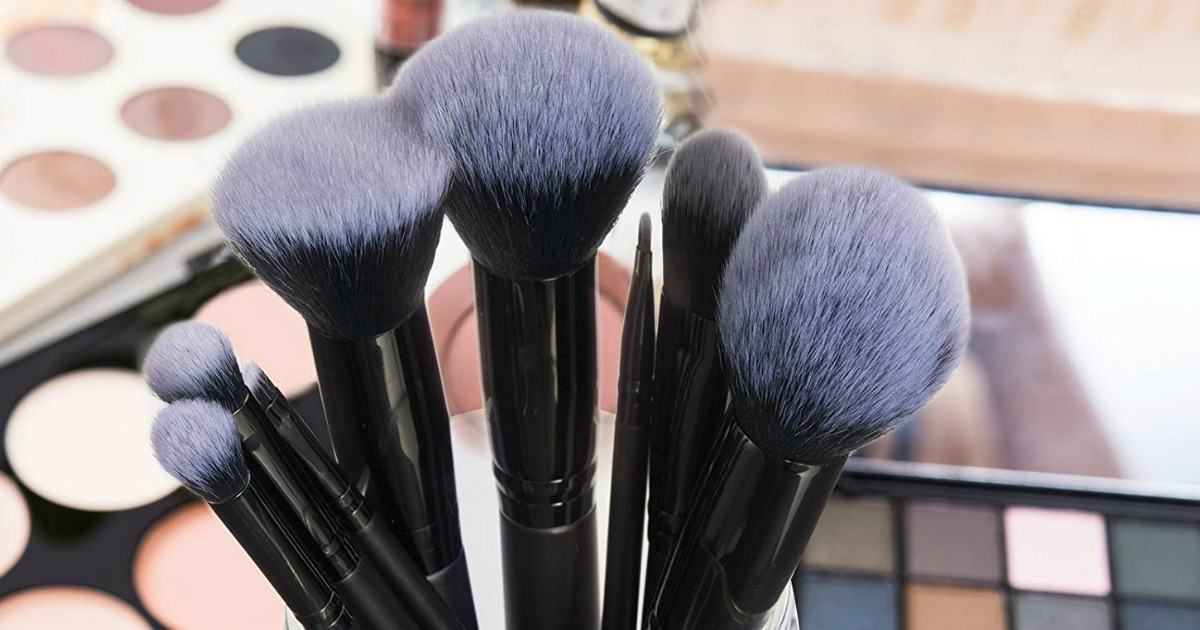 brushes held up with makeup in background