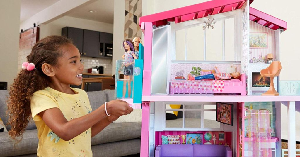 little girl playing with barbie dream house