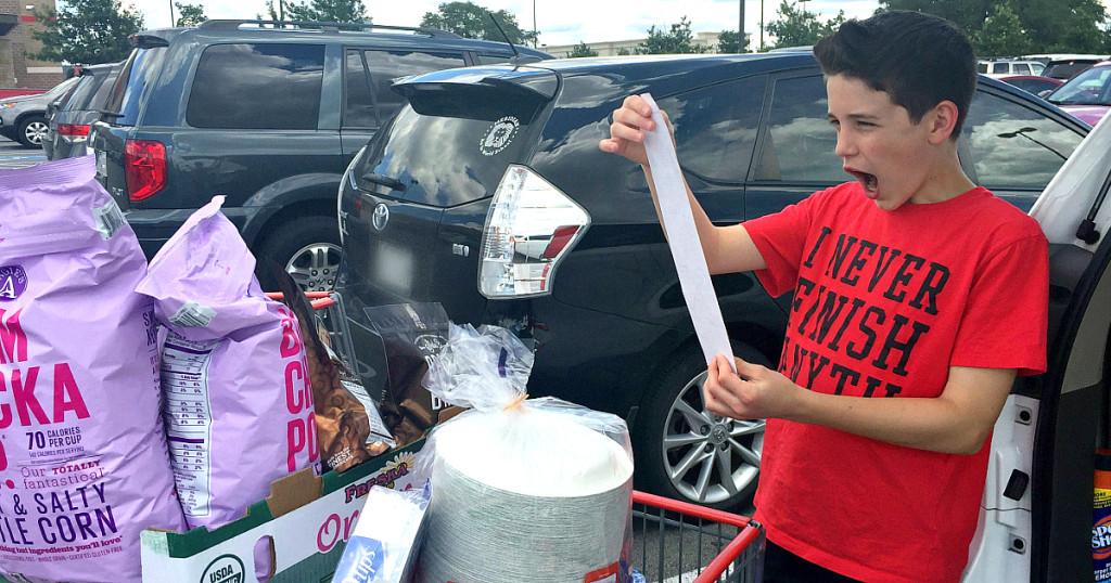 boy holding long Costco receipt in parking lot