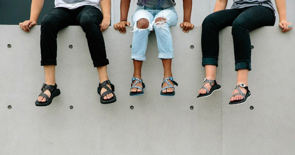 three adults sitting on wall wearing chaco zcloud sandals