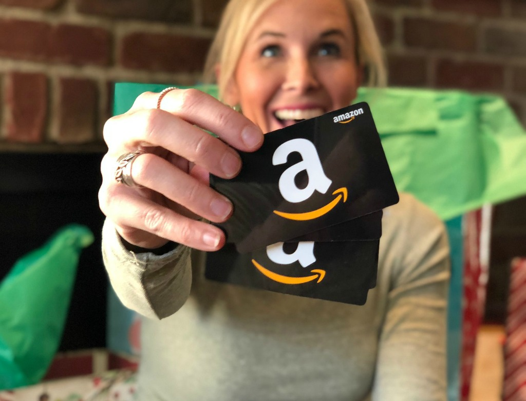 smiling woman holding Amazon gift cards