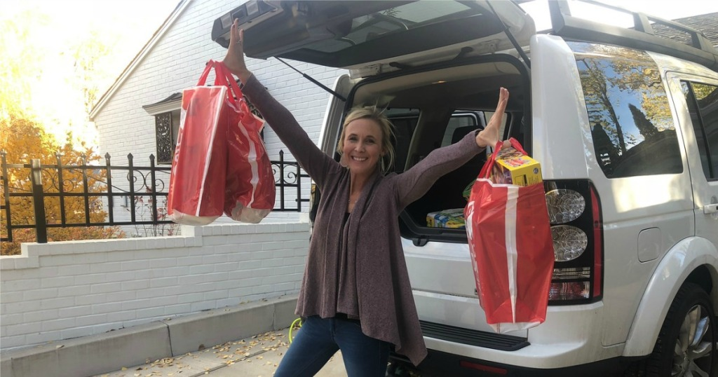 woman holding up Target bags at the back of her SUV