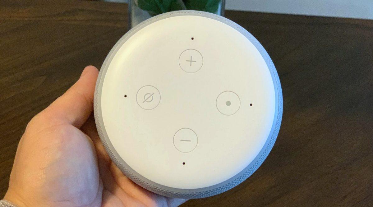 hand holding white smart speaker