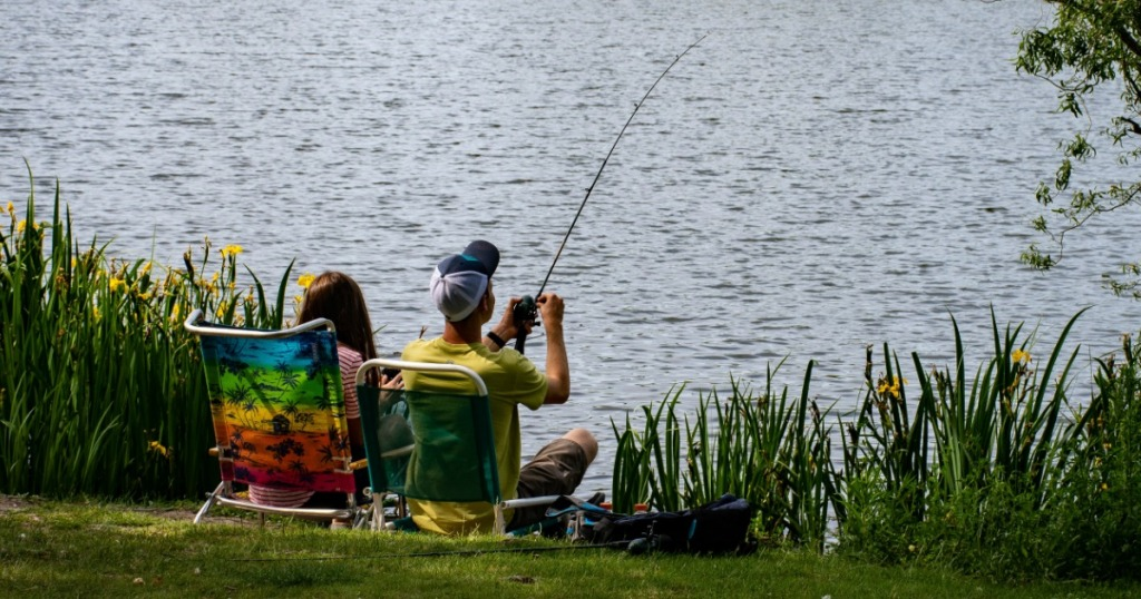couple sitting in chairs fishing at a lake