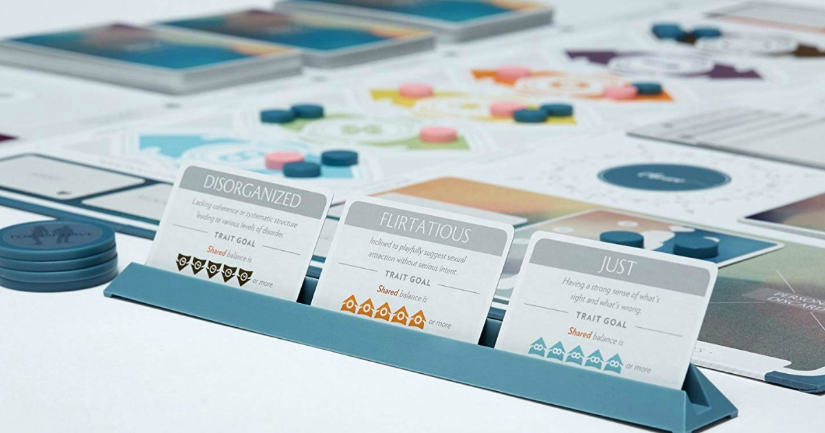 three cards standing in teal tray in front of board game