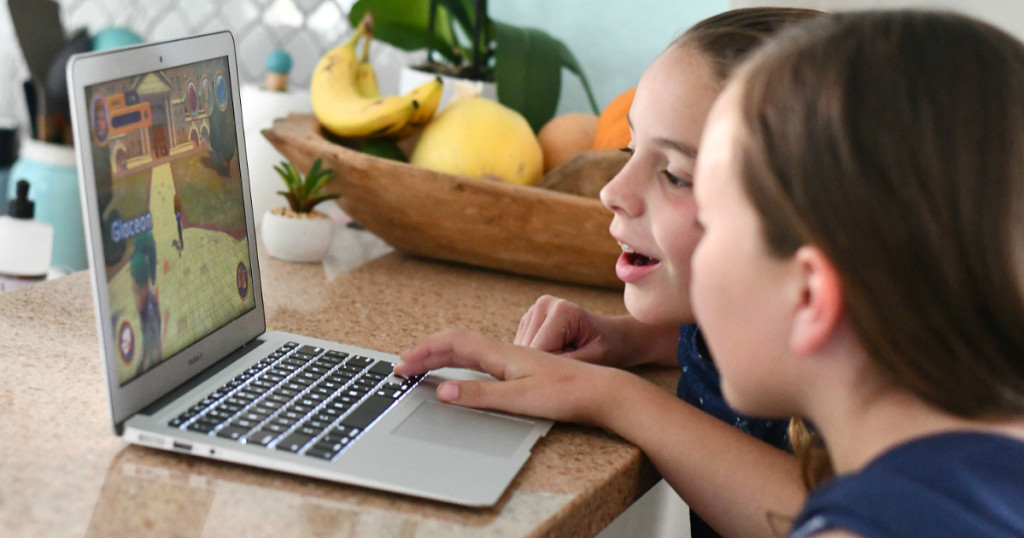 kids smiling and playing on a laptop