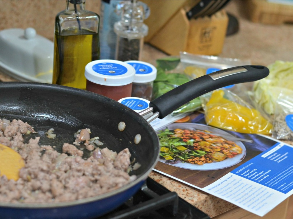 green chef ingredients and pan cooking on stove