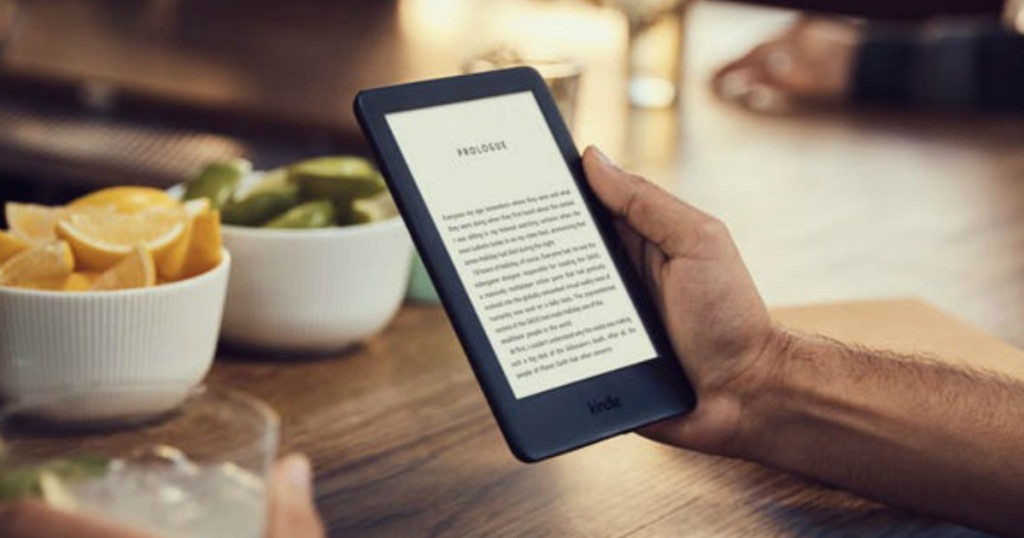 hand holding a kindle near a kitchen table with bowls