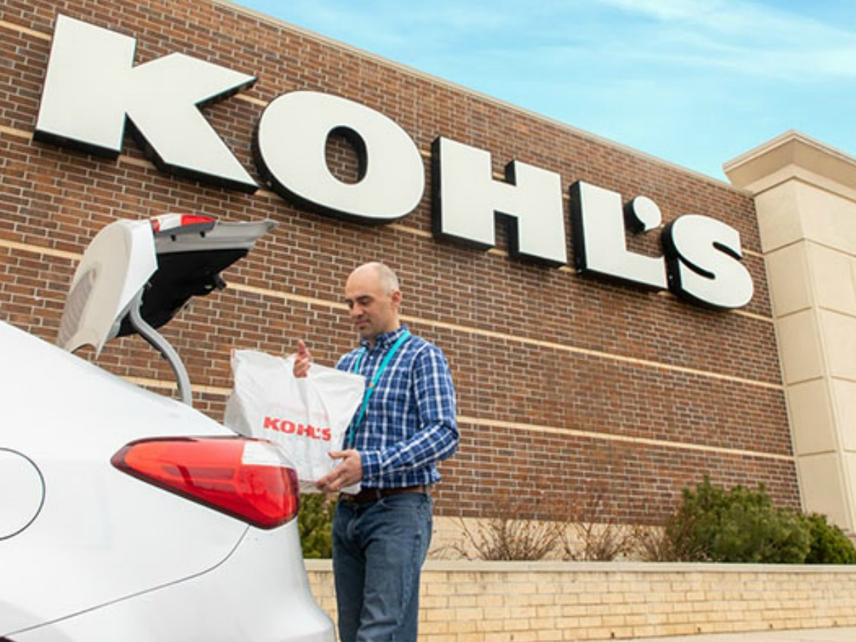 Kohl's employee placing a kohl's shopping bag into the trunk of a car