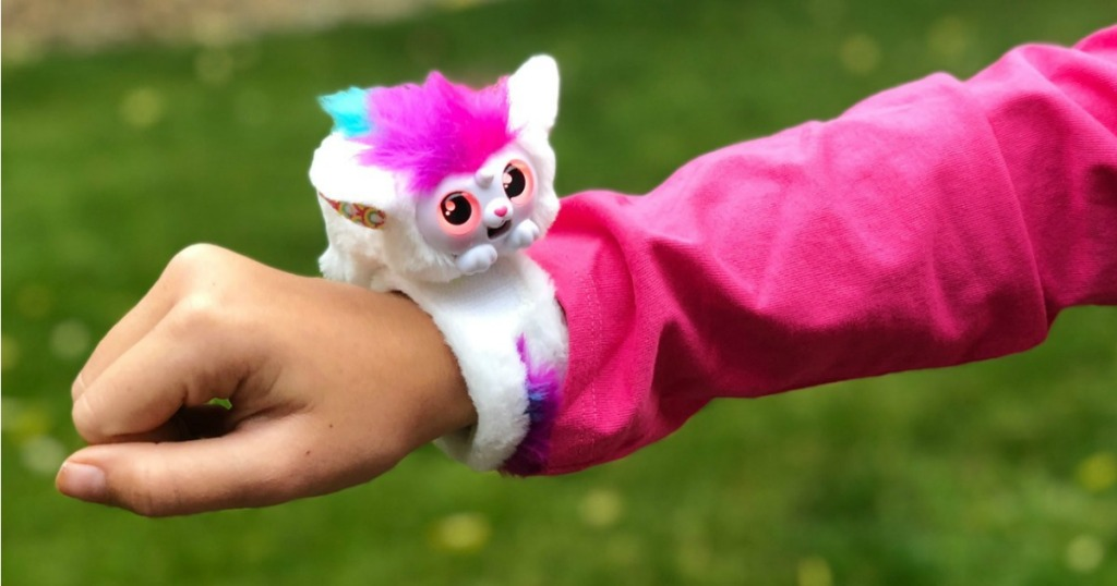 little live wrapples in white and pink on wrist of girl wearing a pink jacket outside