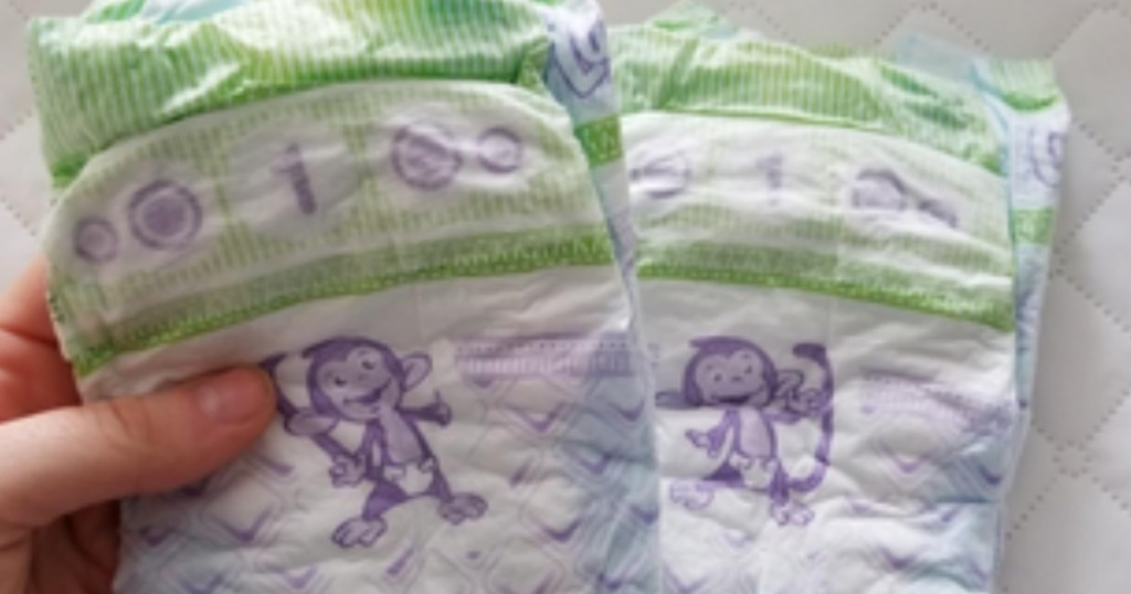 hand holding diapers with monkey picture on them