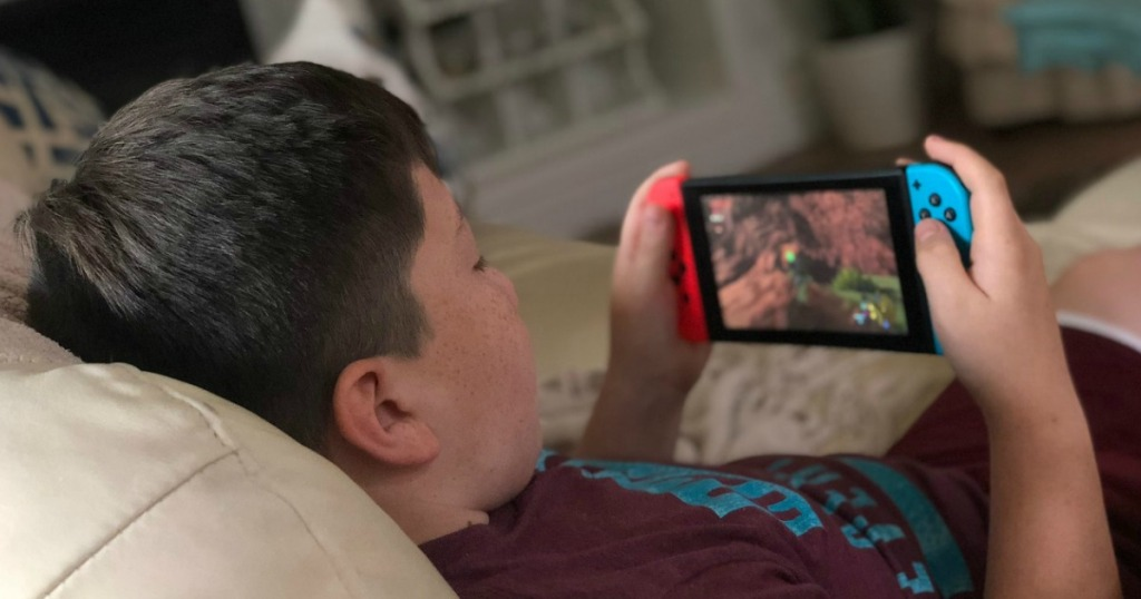 Boy laying on couch playing Nintendo Switch