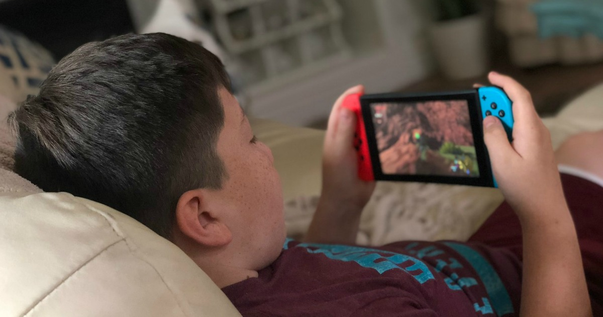 young boy playing nintendo switch while lounging on couch