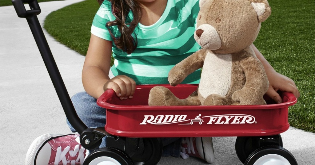 kid playing with a Radio Flyer Mini Wagon and a bear