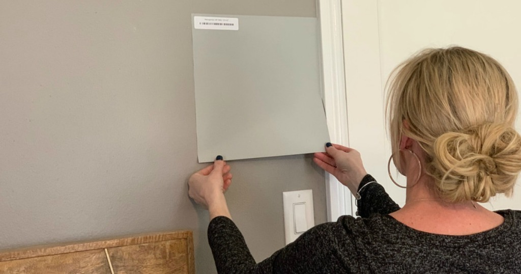 woman putting large square paint sample on wall home decor ideas