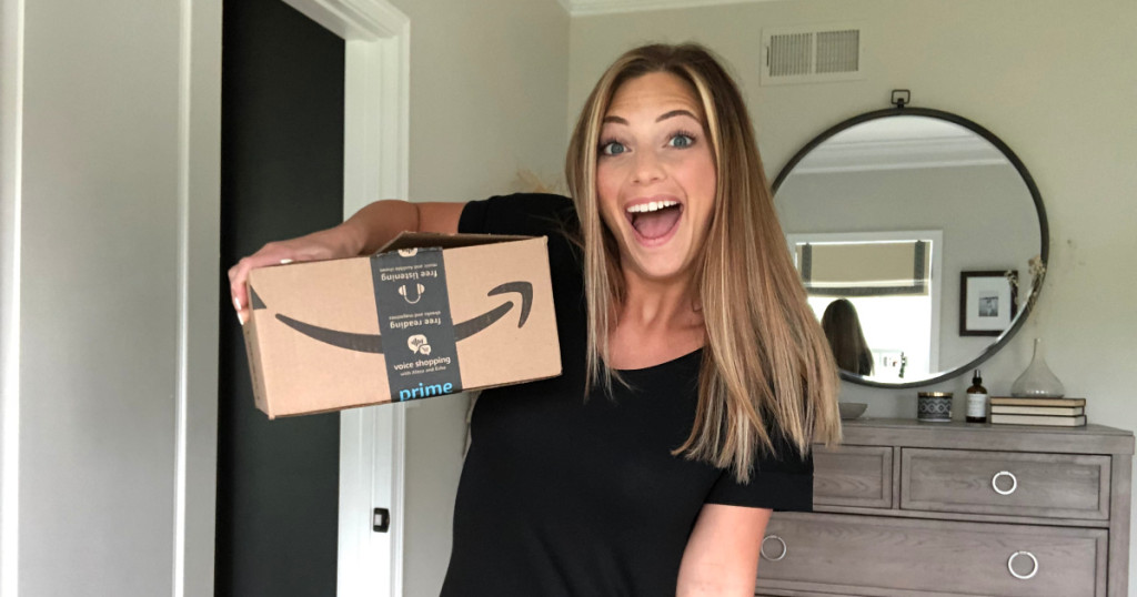 Woman with excited smile holding a large Amazon shipping box