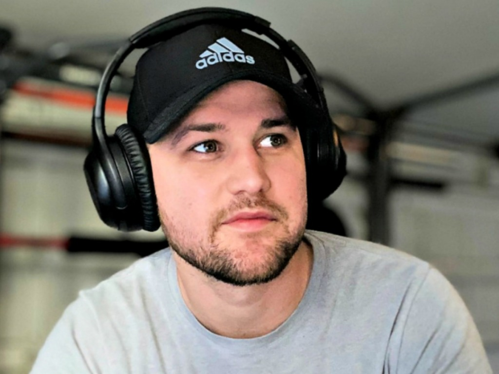 Man with headphones and adidas brand hat on