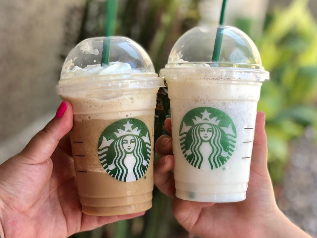 two hands holding Starbucks Frappuccinos with blurred outdoor background