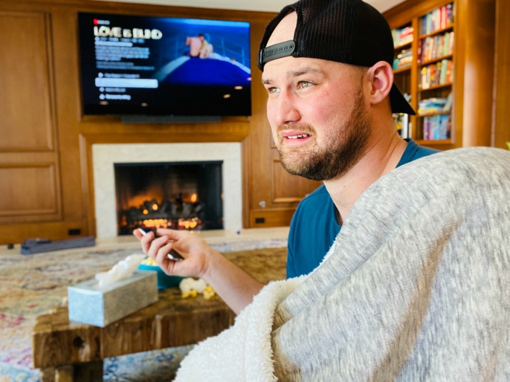 man with sad face wearing blanket and watching tv