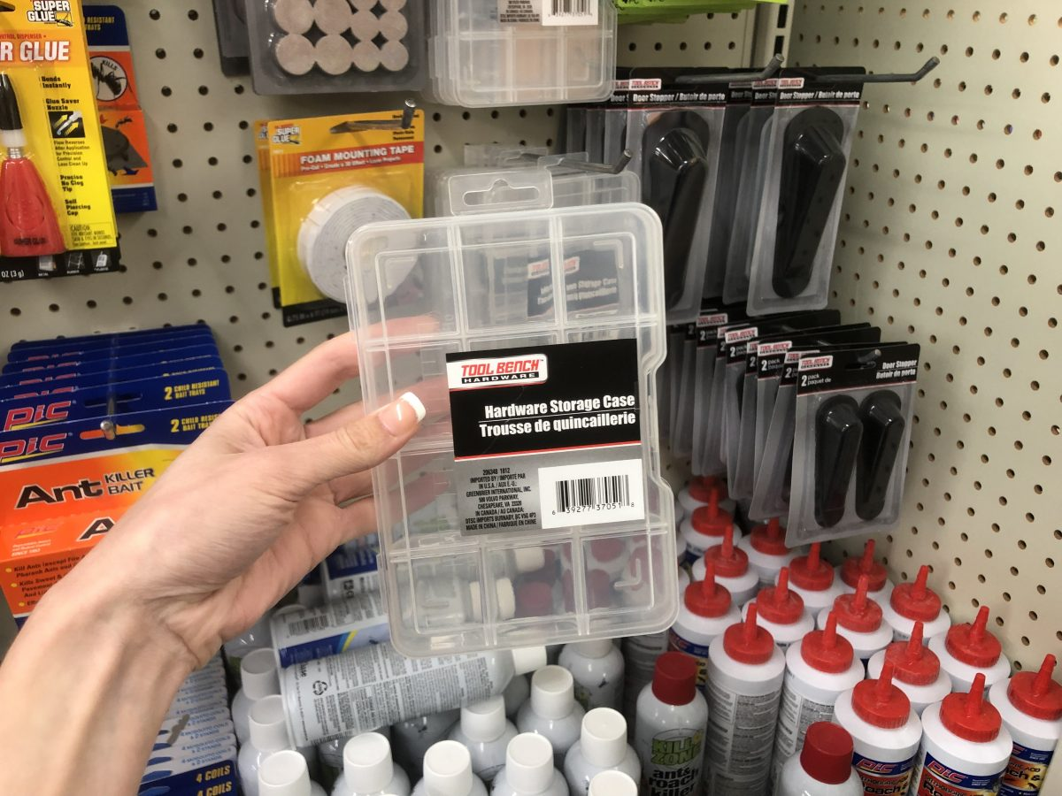 hand holding a hardware storage case in store aisle