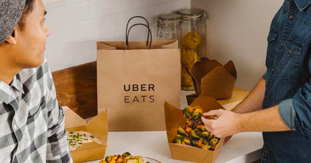 uber eats bag sitting on counter with food and people around it
