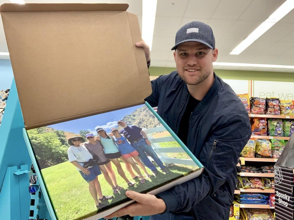 pria yang memegang foto kanvas dalam sebuah kotak