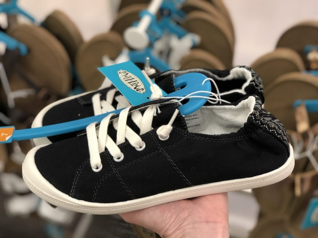 Hand holding up a pair of Women's Mad Love Lennie Sneakers