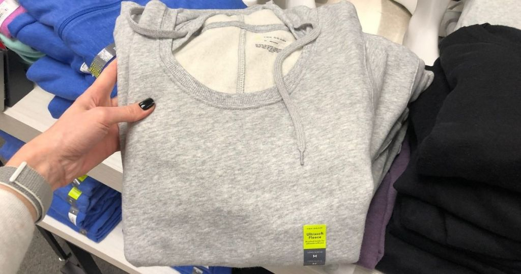 Woman holding up sweatshirt in store