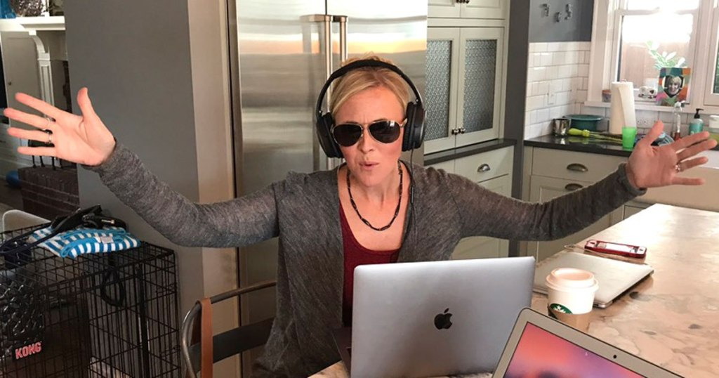woman wearing headphones in front of laptop in kitchen