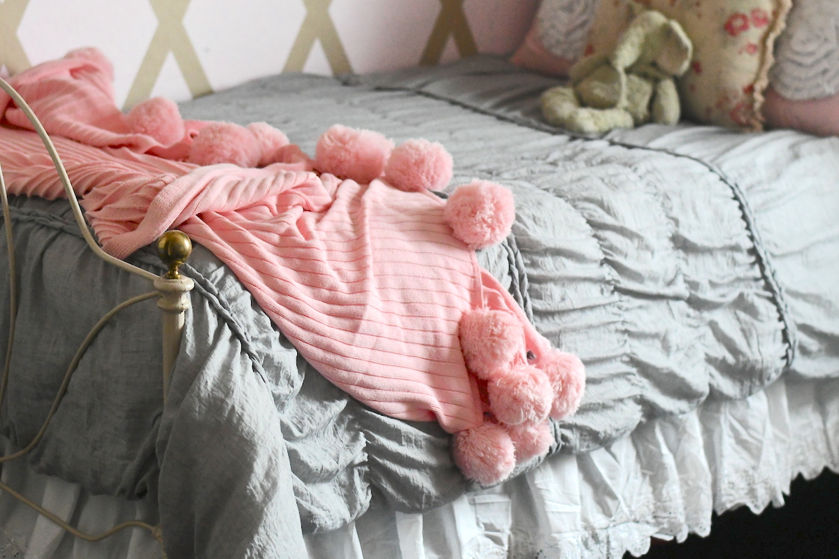 pink pom blanket laying on gray bed