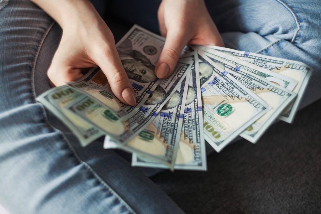 woman holding a fan of cash