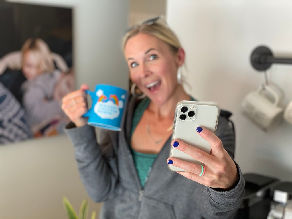 woman holding a mug and cellphone in front of wall photo