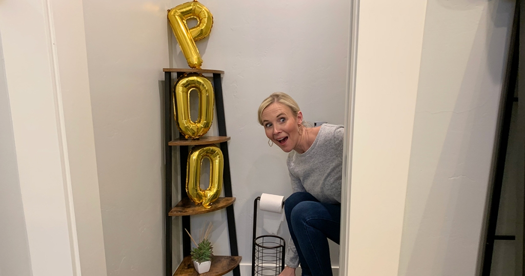 woman sitting on toilet with Poo balloons