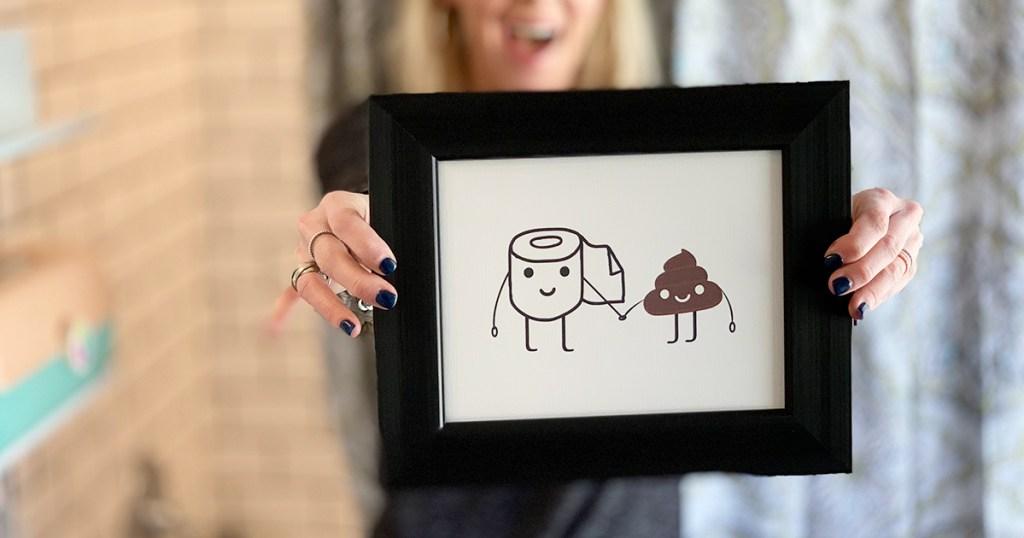 collin holding up framed poop artwork