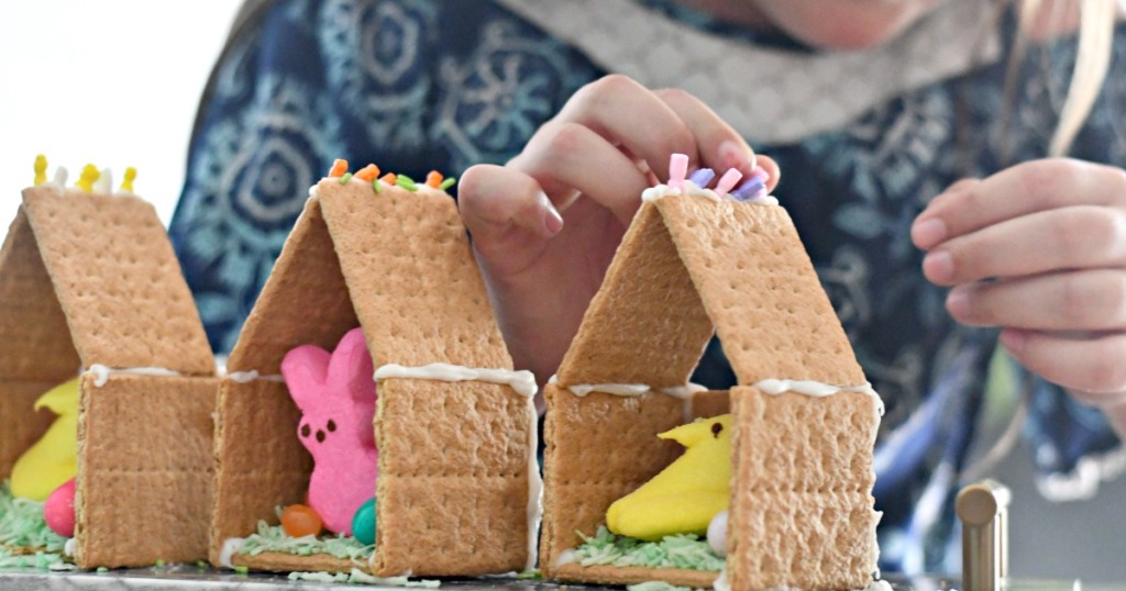 putting together an Easter Peeps house using graham crackers