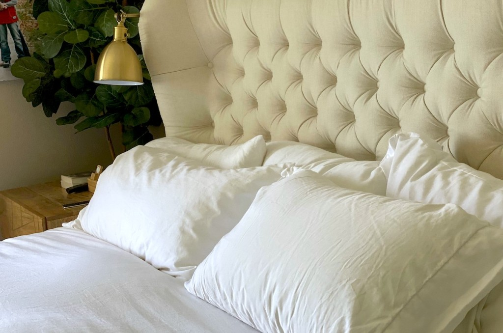 tufted bed headboard with white pillows and sheets on bed