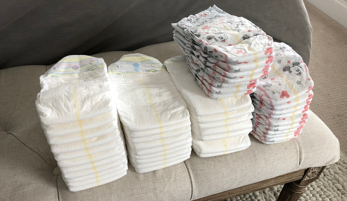 stacks of white and mickey mouse diapers on a tufted bench