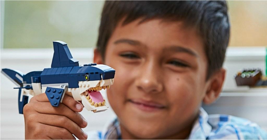 boy holding lego shark