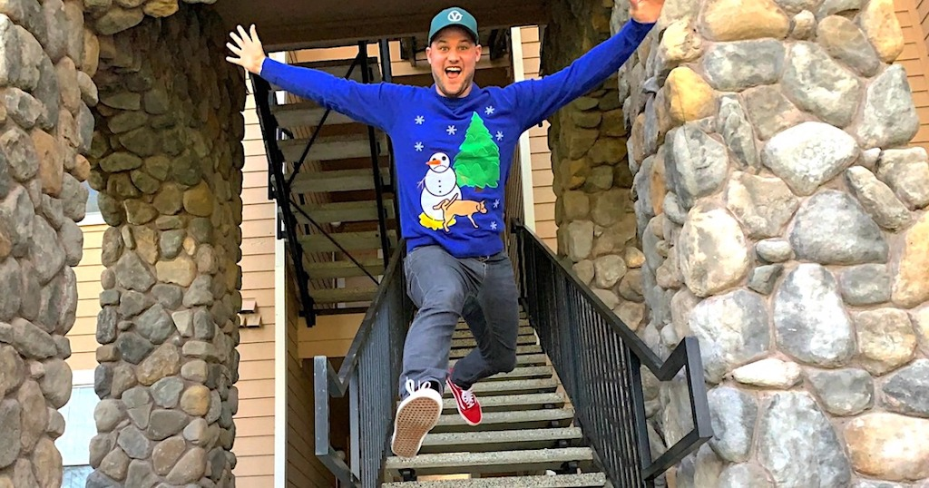 man wearing a Christmas sweater jumping down stairs