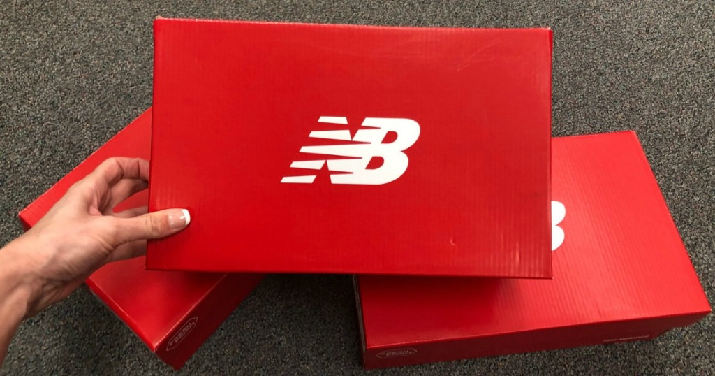 fdd160d1a2d54 hand holding new balance shoe box over two other new balance shoe boxes