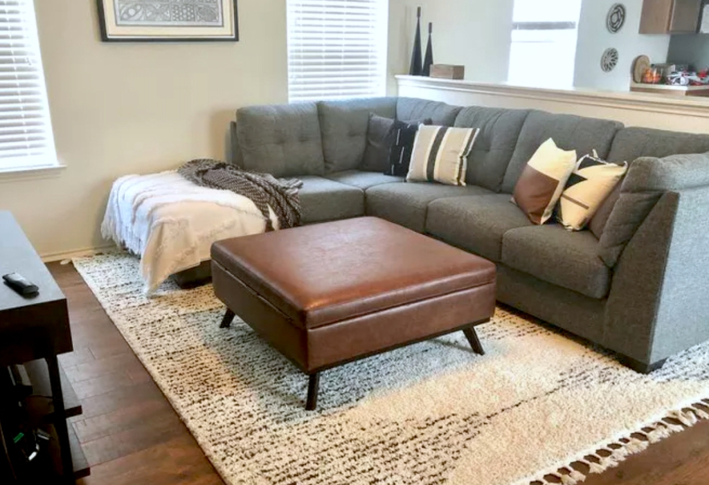 brown leather ottoman in living room with gray couch