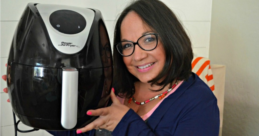 woman smiling holding air fryer