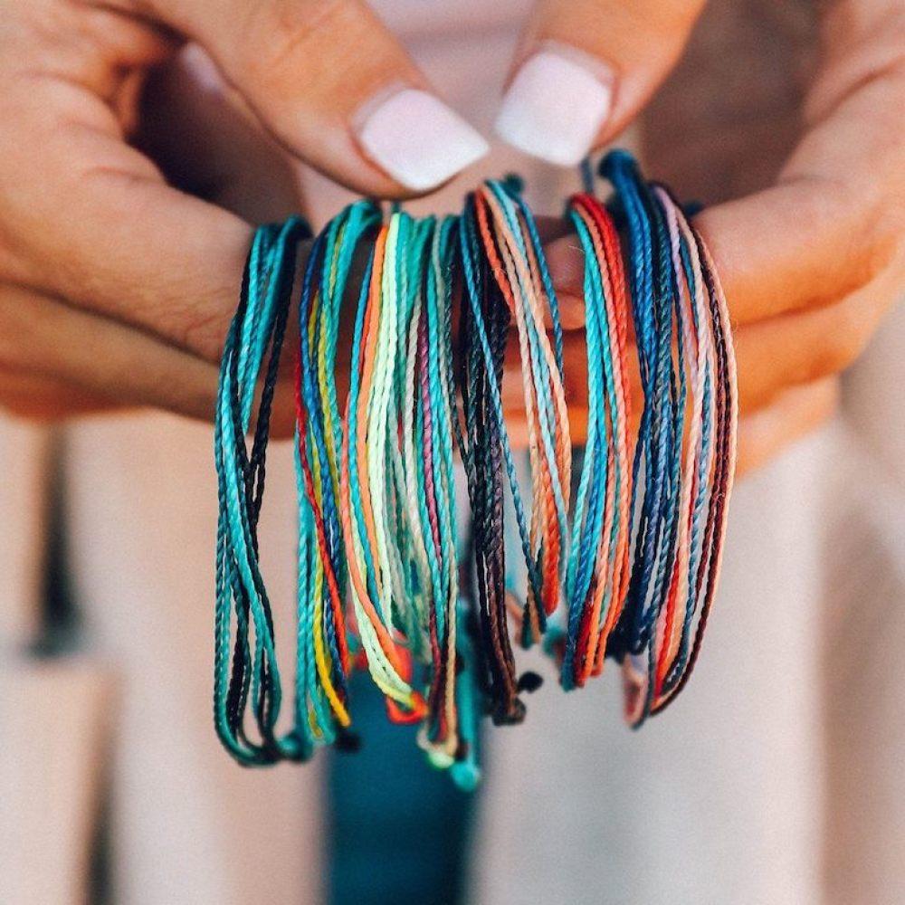 hands holding lot of puravida bracelets originals
