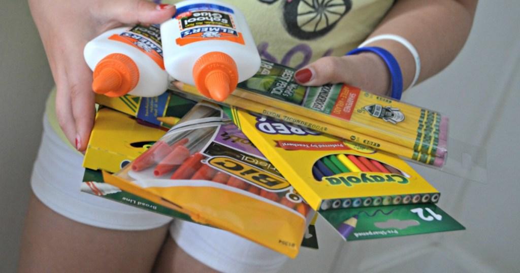 girl holding school supplies