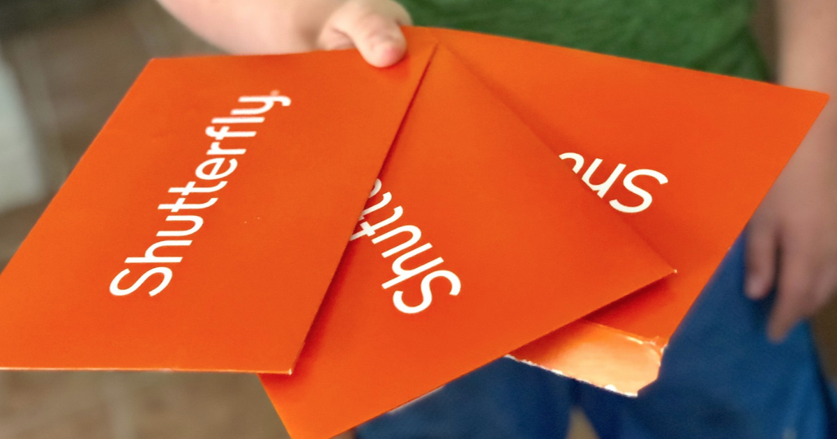 three Shutterfly envelopes held in hand outside