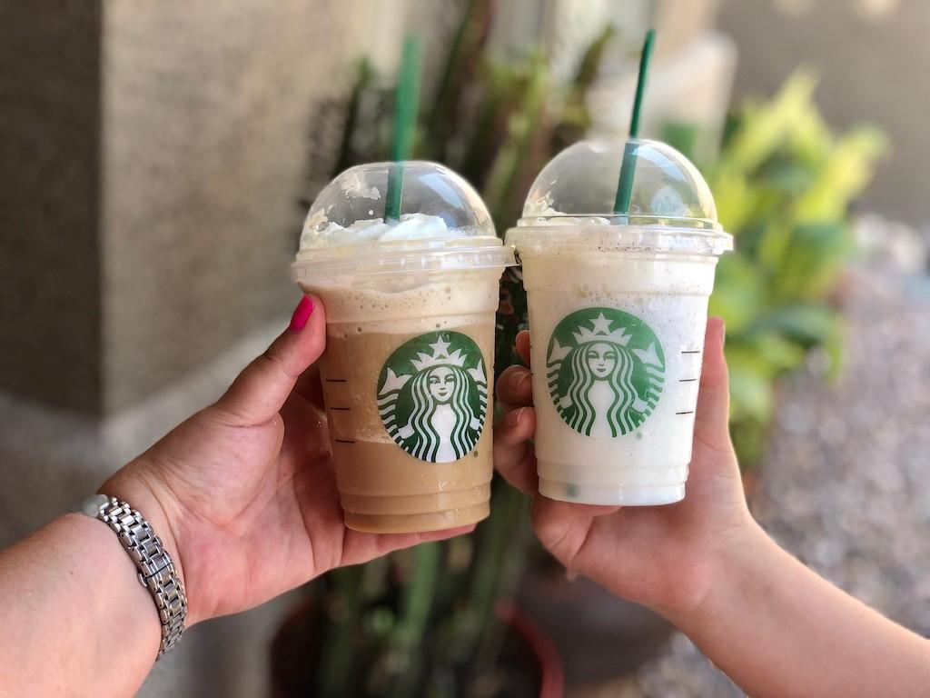 hands holding two starbucks drinks