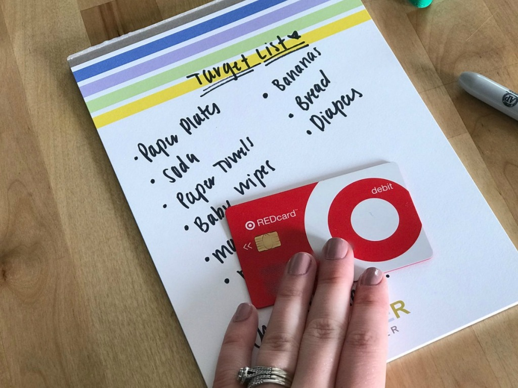 person placing Target debit card on grocery list